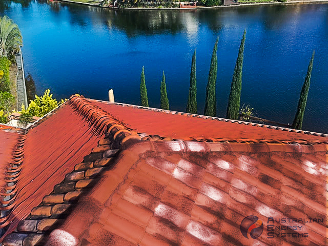 Terracotta coloured solar pool heating roof with a lake view