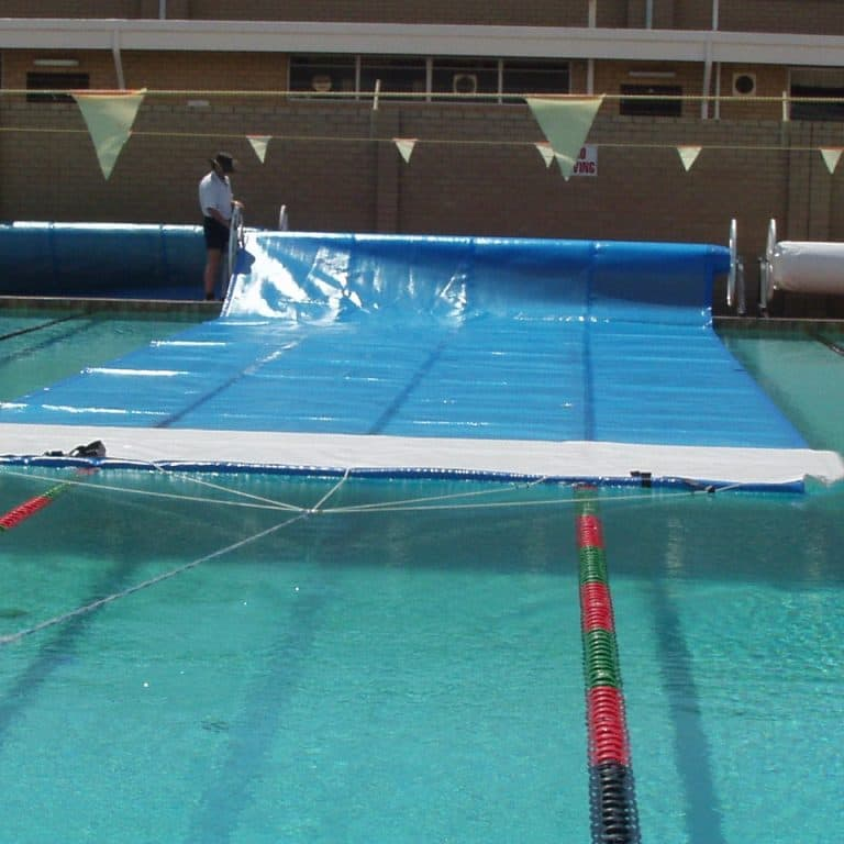 Man unwiniding swimming pool cover