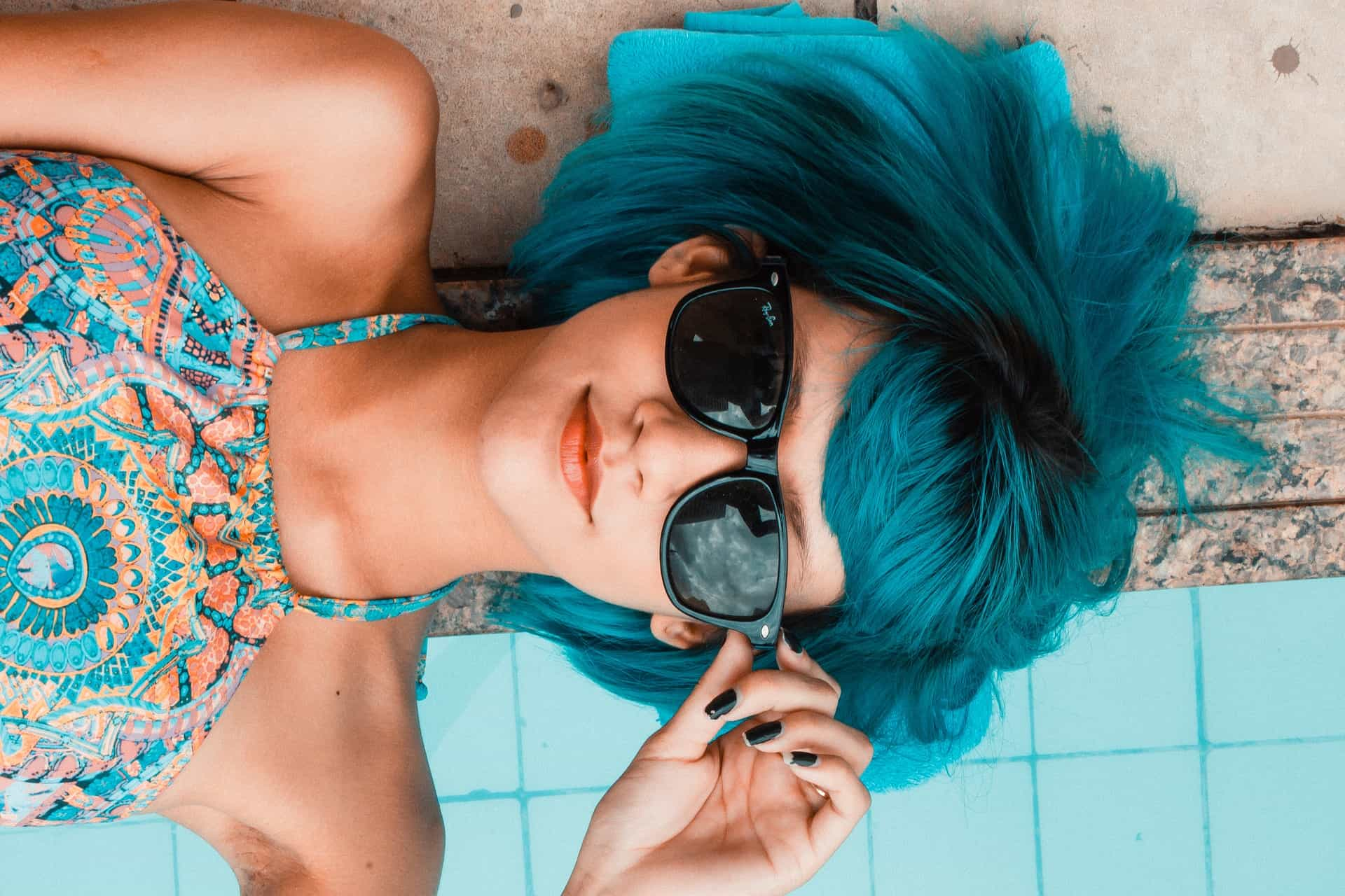 Close up of blue hair girl laying on the edge of pool