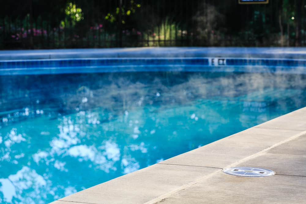 A steaming swimming pool with a concrete edge