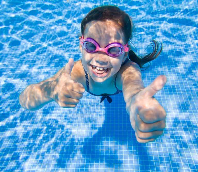 Cheerful little girl playing under water in pool