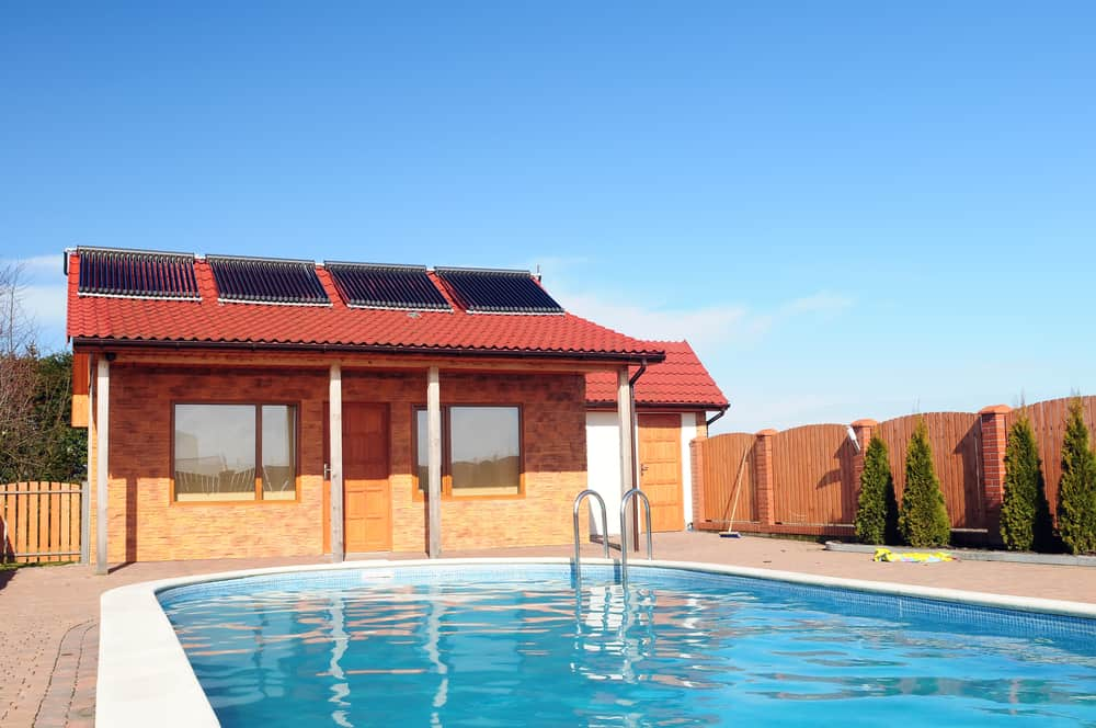 Swimming pool in front of small bungalow with solar panels on roof.