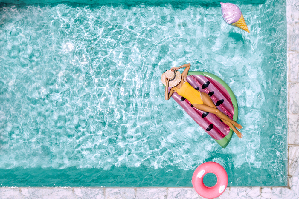 Woman relaxing on watermelon lilo in the pool at private villa. Inflatable ring and mattress. Summer holiday idyllic. High view from above.