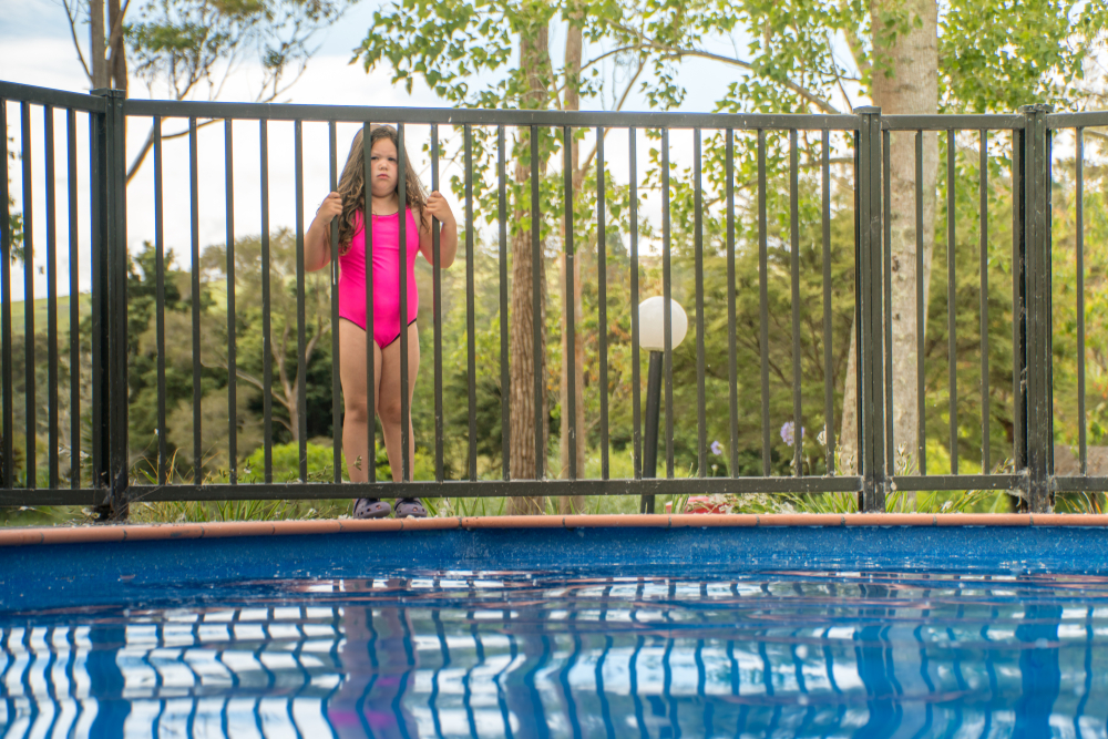 Pool Safety - Young Girl Standing Outside Pool Fence Looking into Pool